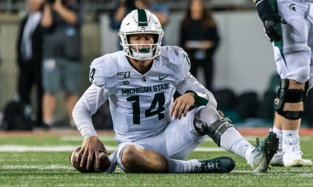 <p>Senior quarterback Brian Lewerke (14) sits on the field after being sacked by the Ohio State defense. The Buckeyes defeated the Spartans, 34-10, on Oct. 5, 2019 at Ohio Stadium.</p>