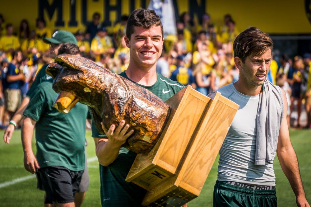 Red-shirt sophomore defender Luke Menne (24) carries the Big Bear Trophy off of the field after the game against the University of Michigan on Sept. 17, 2017 at U-M Soccer Stadium. The Spartans defeated the Wolverines, 1-0.