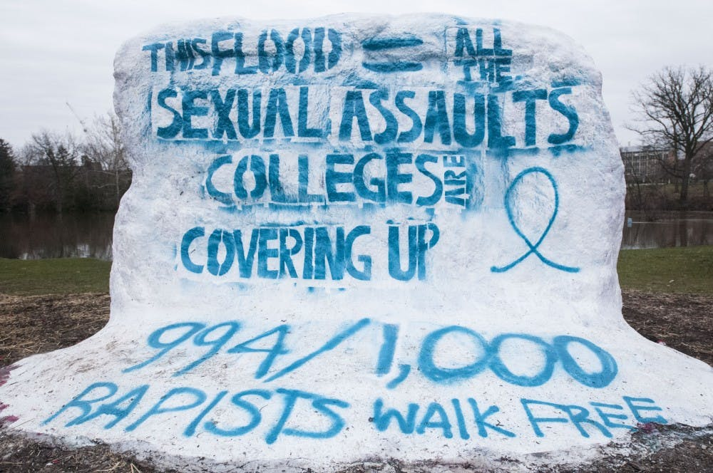 """The Rock reads """"This flood = all the sexual assaults colleges are covering up 994/1,000 rapists walk free."""" on Feb. 22, 2018 at The Rock. The color teal was used to represent sexual assault awareness. (C.J. Weiss 
