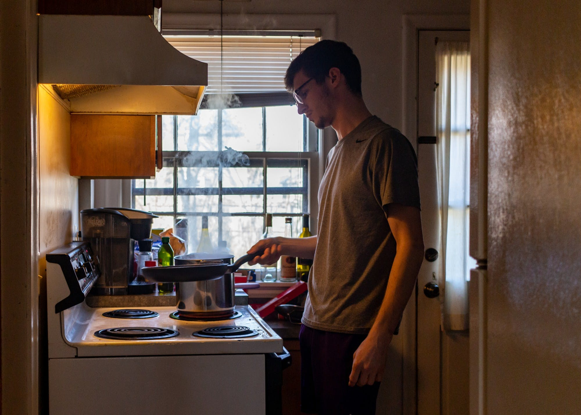 A person wearing glasses, a t-shirt and shorts holds a frying pan above a stove in a kitchen.
