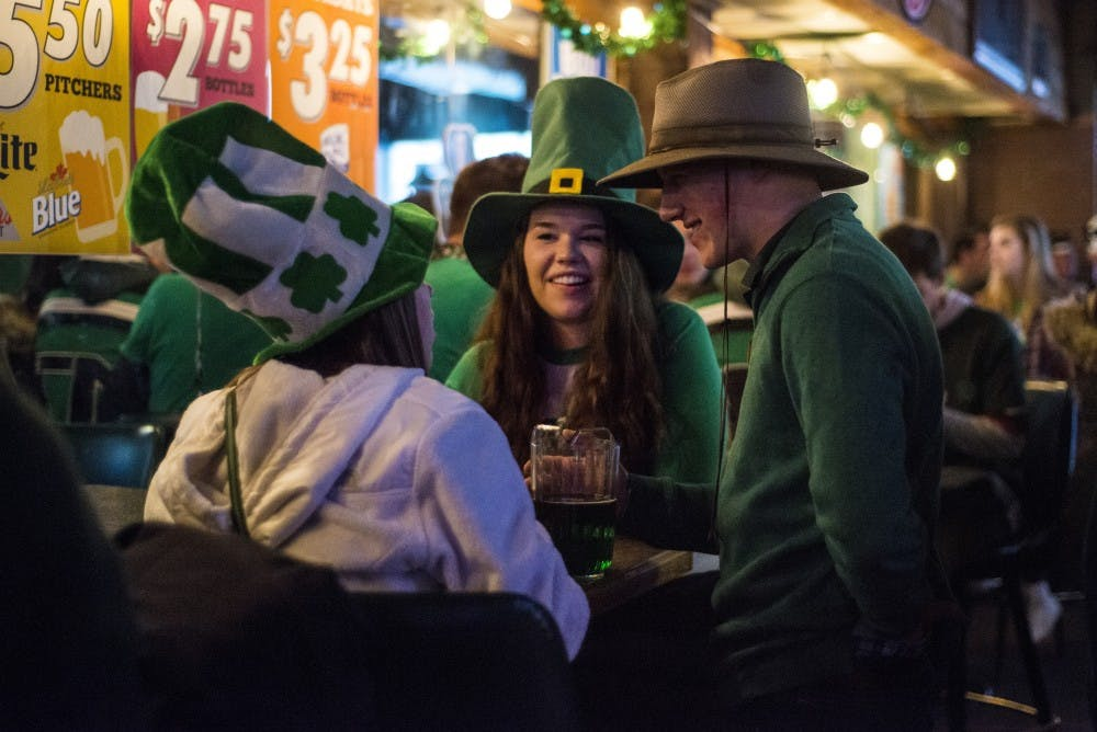 From left to right, environmental biology senior Renee O'Connell, zoology junior Megan White and chemical engineering senior Kevin Klebba converse during St. Patrick's Day on March 17, 2017 at P.T. O'Malley's at 210 Abbot Road in East Lansing.
