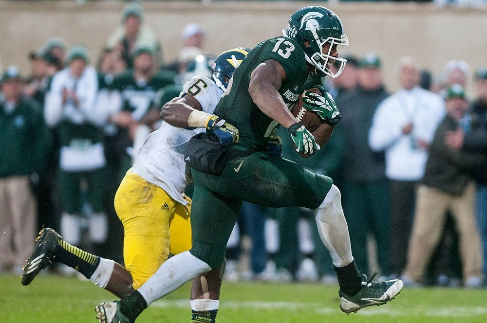 <p>Senior wide receiver Bennie Fowler gets wrapped up by Michigan defensive back Raymon Taylor during the game against Michigan on Nov. 2, 2013, at Spartan Stadium. The Spartans defeated the Wolverines, 29-6. Khoa Nguyen/The State News</p>