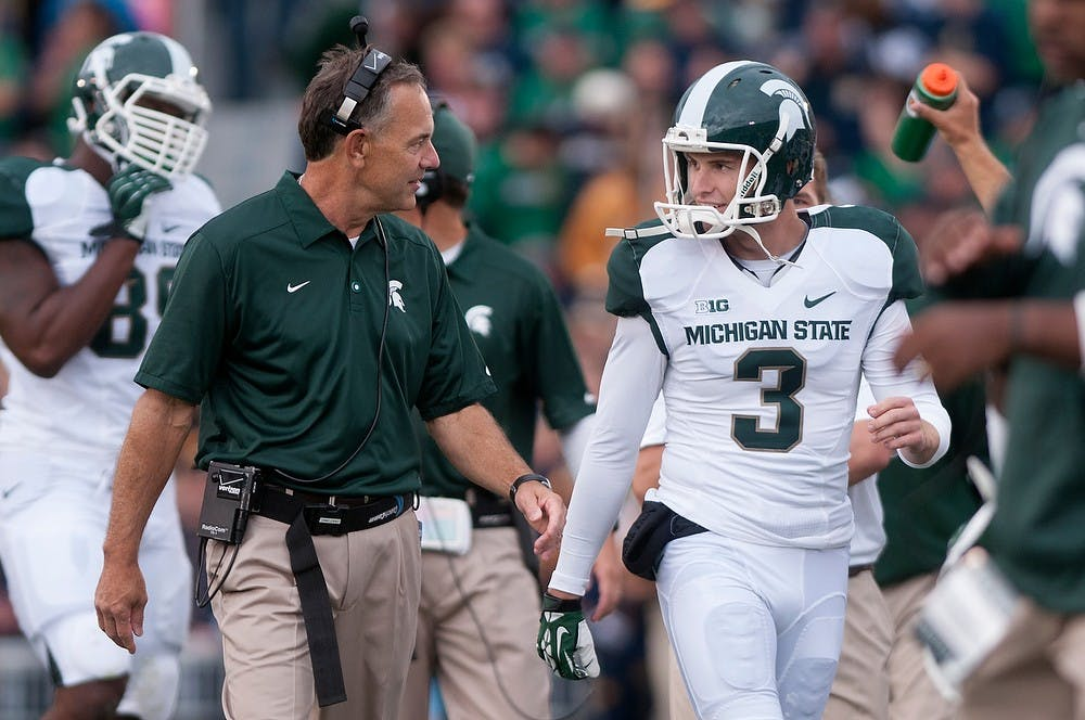 <p>Head coach Mark Dantonio talks to junior punter Mike Sadler during the game against Notre Dame Sept. 21, 2013, at Notre Dame Stadium in South Bend, Ind. The Fighting Irish defeated the Spartans 17-13. Julia Nagy/The State News</p>