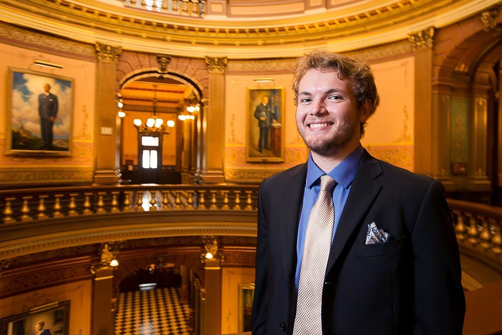 <p>Social relations and policy and comparative cultures and politics senior Ryan Miller poses for a portrait, August 1, 2014, at the Michigan State Capitol. Miller is interning with the Michigan House of Representatives. Corey Damocles/The State News </p>