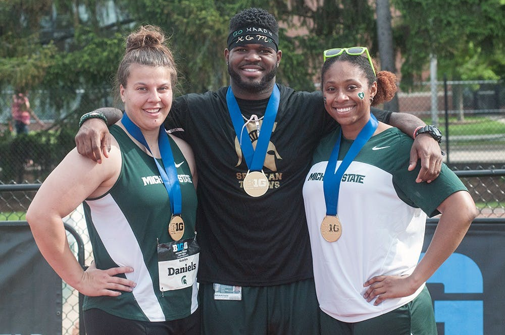<p>Freshman Katelyn Daniels (left), senior Antonio James (right) and junior Cynthia Watt pose for a picture on May 16, 2015 after taking the Big Ten titles in their respective throwing events. Ryan Squanda/The State News</p>