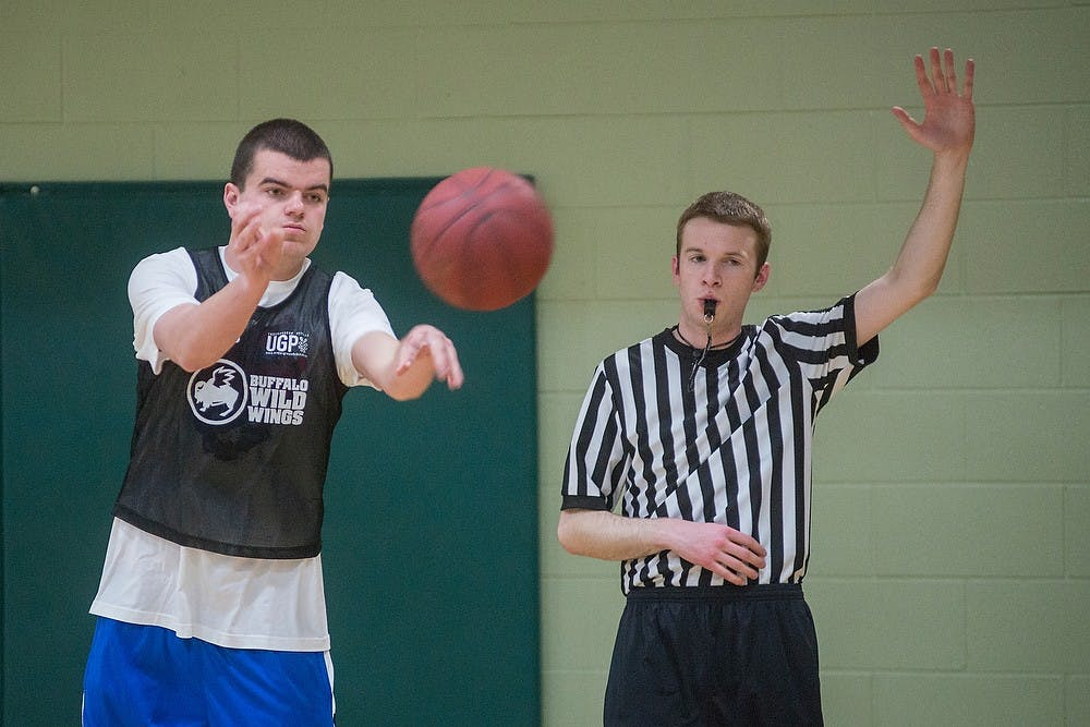 <p>Accounting freshman Kevin Wenner passes the ball as social studies education senior Chad Stevens starts the clock on Mar. 18, 2015, while working as an IM official supervisor during an intramural basketball game at IM Sports East. Stevens has been a referee for IM Sports for 3 years and referees for basketball games at IM Sports facilities at least 3 nights a week. Emily Nagle/The State News</p>