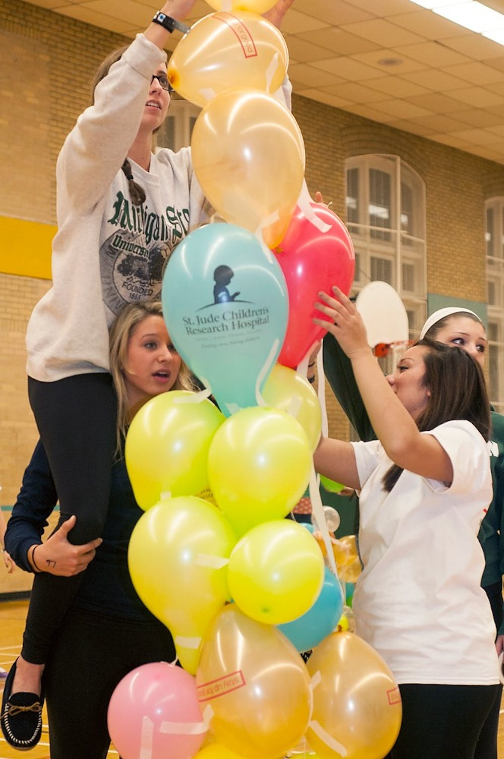 <p>Pre-medical freshman Jaqui Somes sits on the shoulders of supply chain management freshman Jamie Ulanch while while building a balloon tower with teammates Nov. 15, 2013, at IM Sports-Circle. Students stayed up all night playing games, watching videos and eating to celebrate their fundraising for St. Judes research hospital.</p>