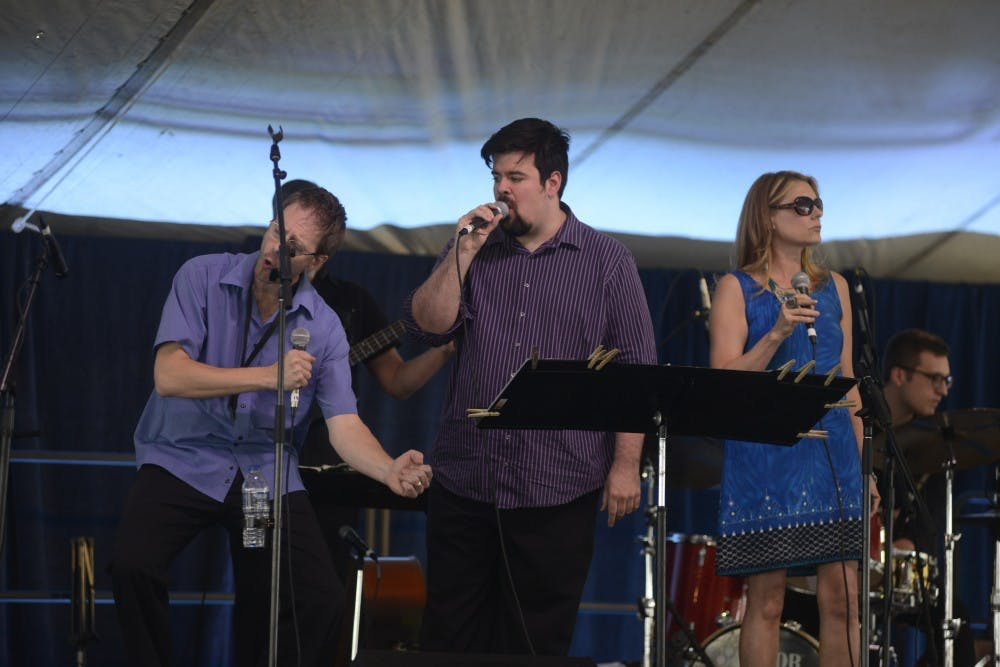 <p>Three of the four members of the Metro Jazz Voices featuring (left to right) Carl Cafagna who also plays the saxophone and the flute, Jeremy St. Martin and Meri Slaven during the East Lansing Summer Solstice Jazz Festival near Ann Street Plaza June 19th. 2015. Wyatt Giangrande/The State News</p>