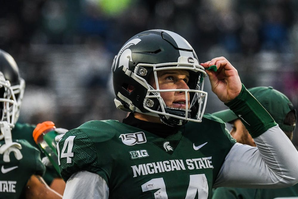Senior quarterback Brian Lewerke (14) looks at the scoreboard during the game on Nov. 30, 2019 at Spartan Stadium. The Spartans lead 13-7 against the Terrapins at halftime.