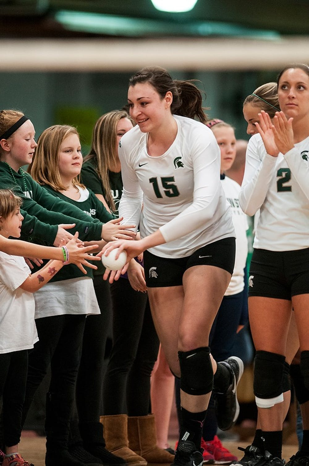 <p>Senior outside hitter Lauren Wicinski high-fives some young fans before the game against Minnesota on Nov. 23, 2013, at Jenison Field House. The Spartans lost to the Golden Gophers, 3-1. Khoa Nguyen/The State News </p>