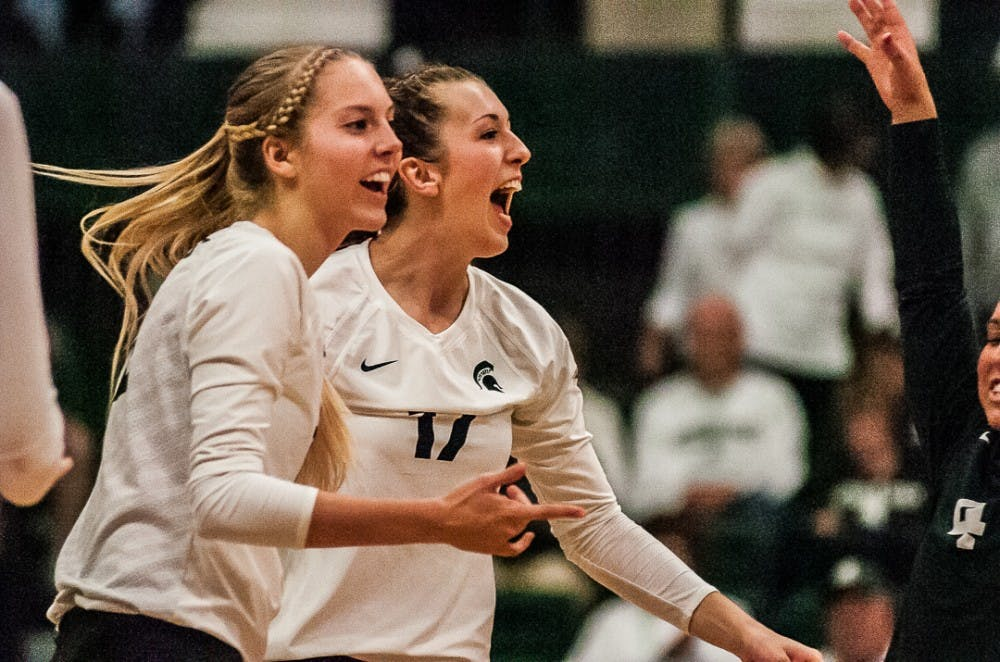 Senior setter Rachel Minarick (12) and senior middle blocker Alyssa Garvelink (17) react during the game against Michigan on Oct. 18, 2017 at Jenison Fieldhouse. The Spartans secured a 3-1 win against the Wolverines.