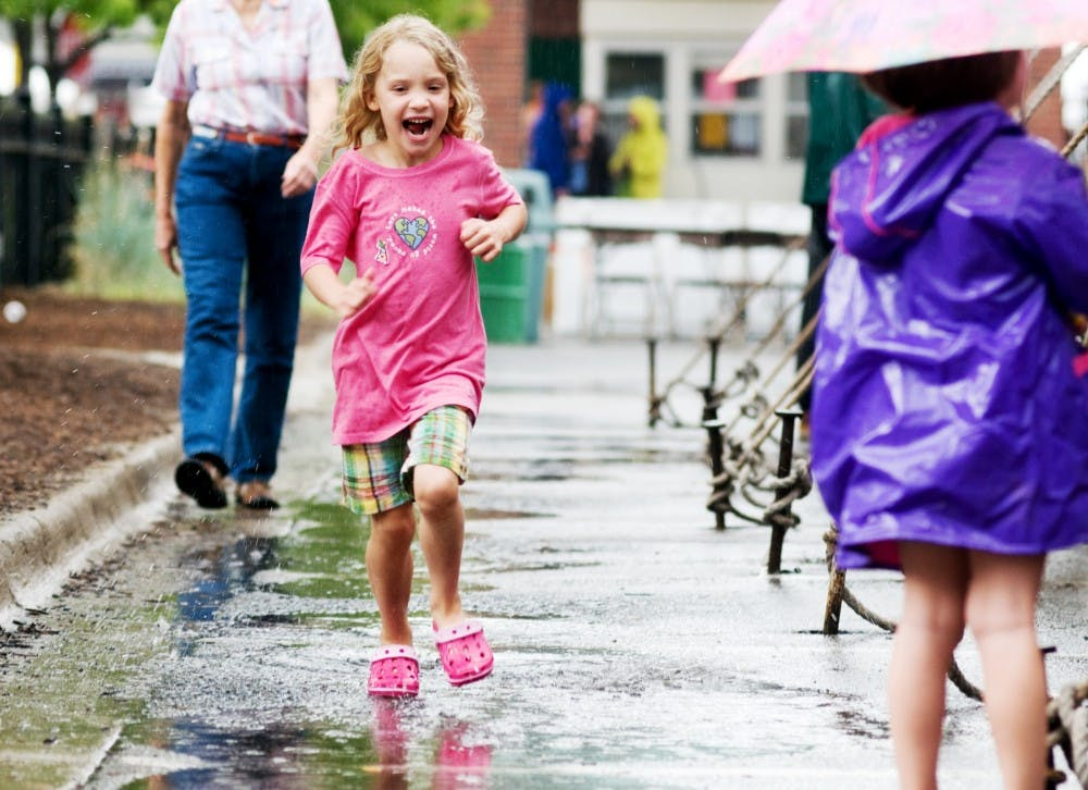 <p>Grand Ledge resident Madeline Gooley, 6, runs through puddles as the rain lets up Sunday at the Great Lakes Folk Festival held in East Lansing. </p>
