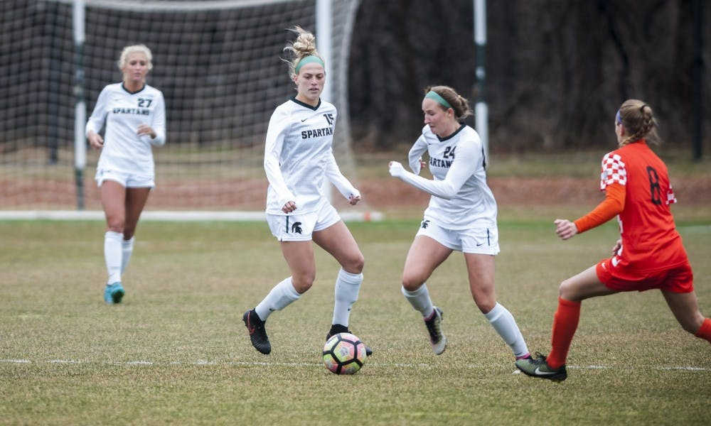 Freshman midfielder Sadie Misiewicz (24) attempts to dribble past Bowling Green defender Alexis Fricke (8) during the game against Bowling Green State University on March 25, 2017 at DeMartin Stadium. The Spartans defeated the Falcons, 5-1.