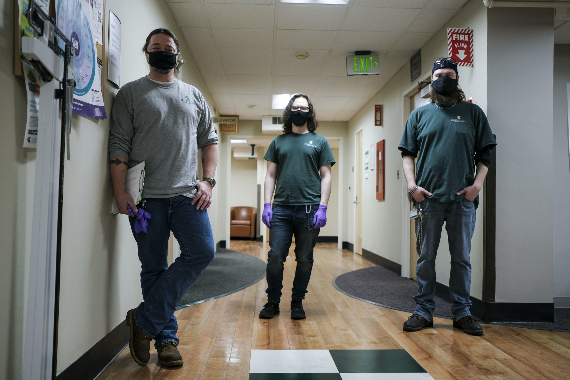 Three people all wearing masks, jeans, work boots and shirts with the Michigan State Spartan logo on them stand slightly apart in a medical building hallway to pose for a photo.