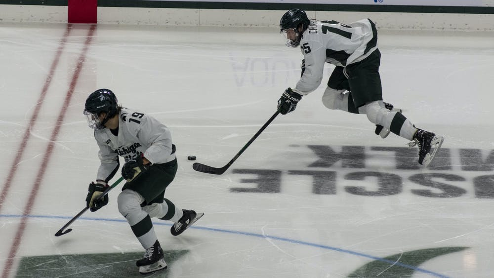 Junior left defenseman Christian Krygier (15) and sophomore right wing Nicolas Müller (19) pass the puck back and forth to each other during the third period. The Spartans triumphed against the Sun Devils, 2-0, on November 20, 2020.