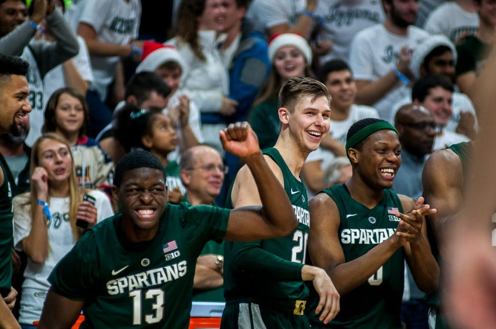 Freshman forward Gabe Brown (13), senior guard Matt McQuaid (21) and junior guard Cassius Winston (5) cheer during the game against Tenessee Tech on Nov. 18, 2018 at the Breslin Center. The Spartans beat the Golden Eagles, 101-33.