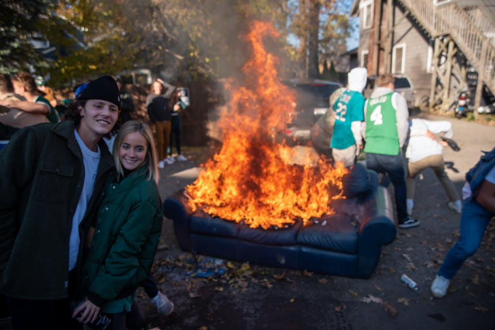<p>Michigan State University Students posing for pictures in front of burning couch in alley off of Division St on Saturday, October 31, 2020.</p>