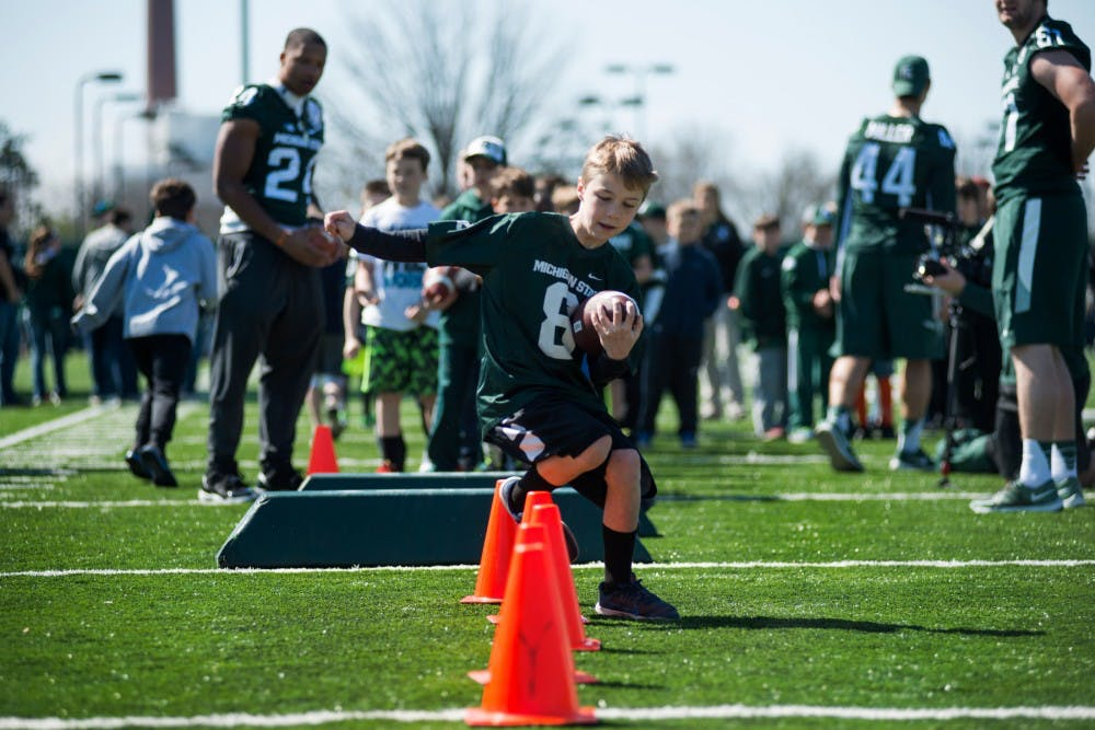 Spring Lake, Mich. resident Sam Bajt, 9, runs through a series of cones during a drill on April 23, 2016 at the practice fields behind the Duffy Daugherty Football Building. MSU's coaching staff and players conducted a free youth football clinic to stress the fundamentals of football for children ages 8-12.