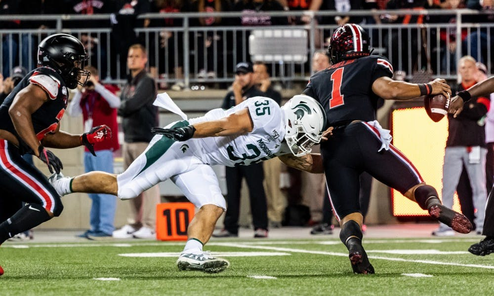 <p>Senior linebacker Joe Bachie (35) sacks Ohio State quarterback Justin Fields (1). The Buckeyes defeated the Spartans, 34-10, on Oct. 5, 2019 at Ohio Stadium. </p>
