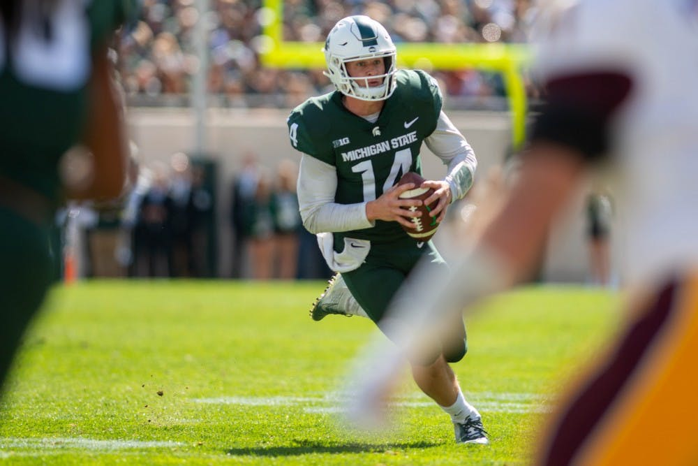 Junior quarterback Brian Lewerke (14) runs with the ball during the game against Central Michigan at Spartan Stadium on Sept. 29, 2018. The Spartans defeated the Chippewas 31-20.
