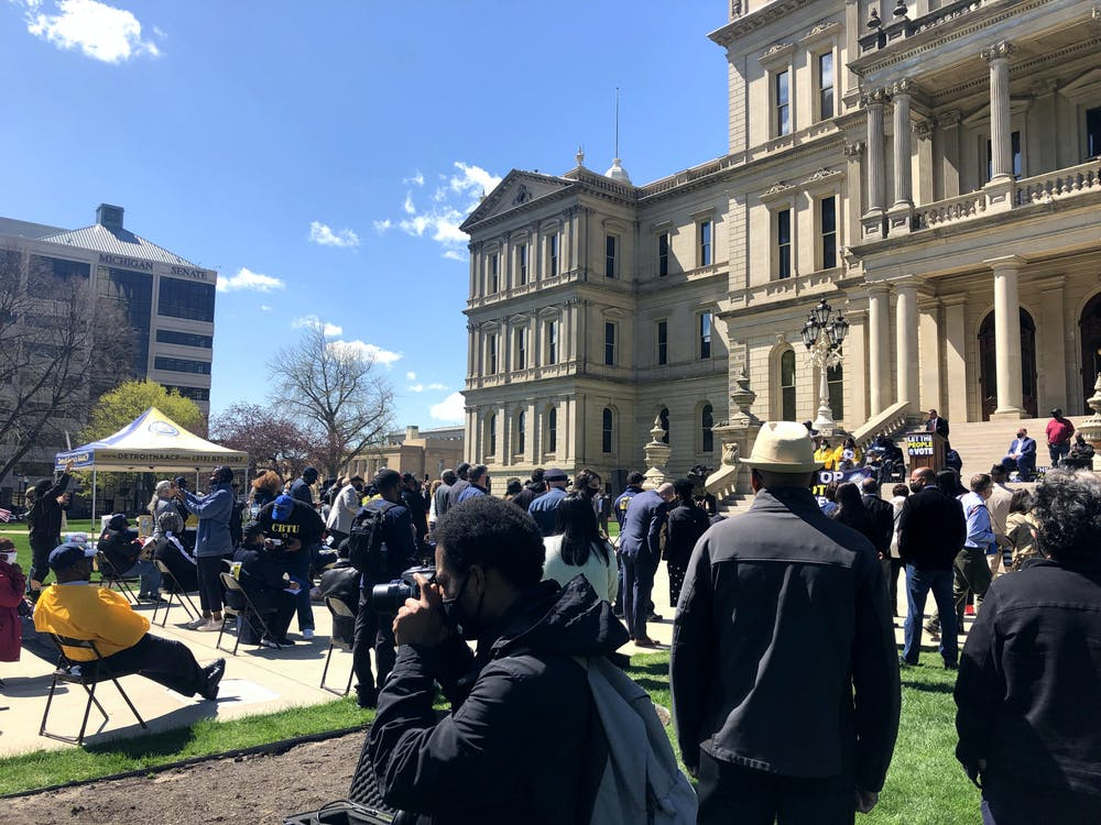 <p>On March 13, 2021, a crowd gathers at the Michigan Capitol building to rally and protest against a set of Republician-proposed voter laws that Democrats and other Michigan civil rights groups say would bring about voter suppression. </p>