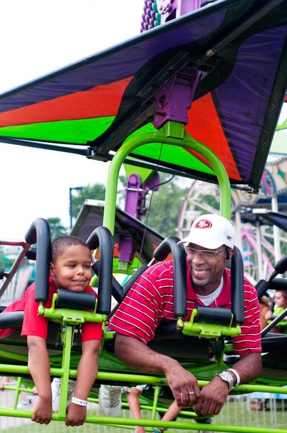 <p>Lansing residents Keith Scott and Keith Scott Jr., 6, enjoy a ride Tuesday afternoon at the ingham County Fair.</p>