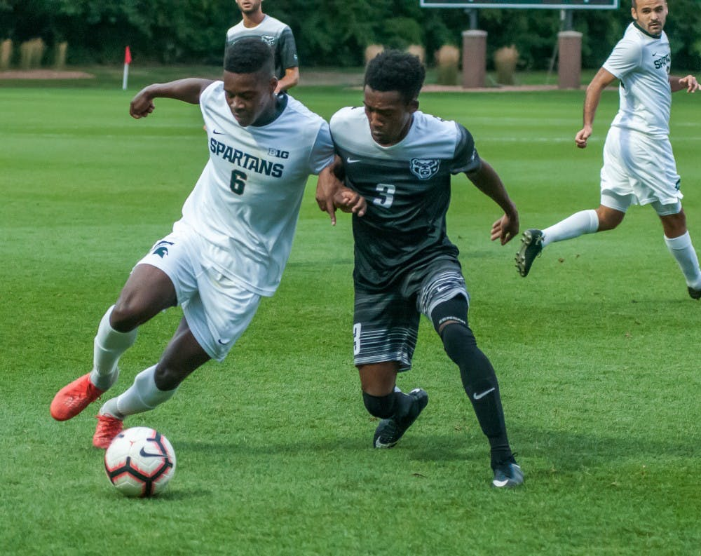 Senior forward Dejuan Jones (6) leans on the defender while bringing the ball up the field during the game against Oakland on Sept. 10, 2018 at DeMartin Stadium. The Spartans defeated the Golden Grizzlies; 4-2.