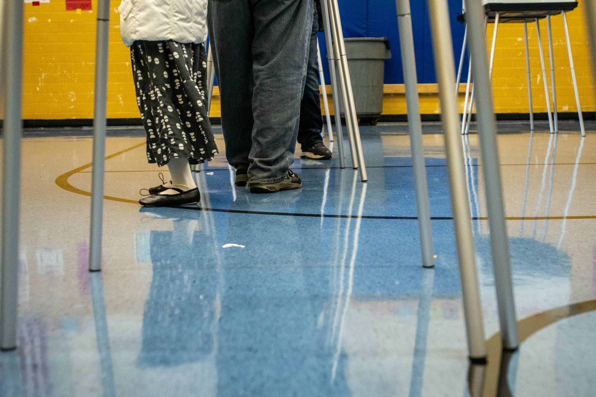 A low-angle photo of voters' legs at the polls.
