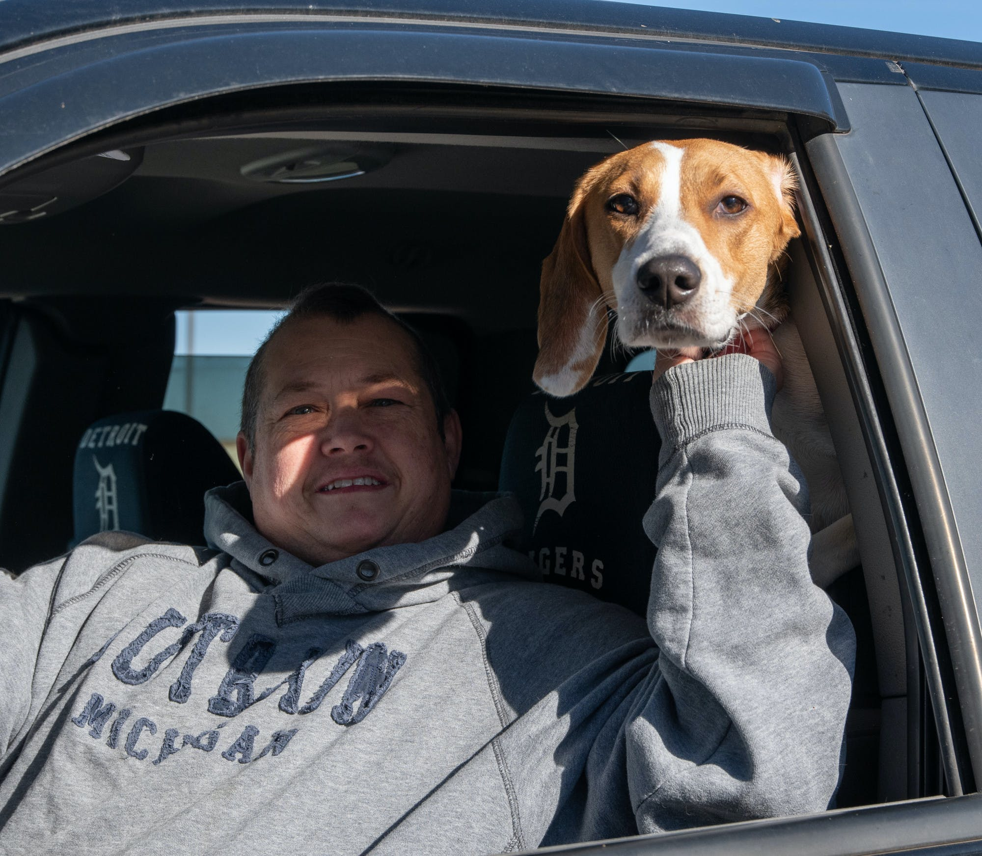 A man and his dog pose for a photo in a car.