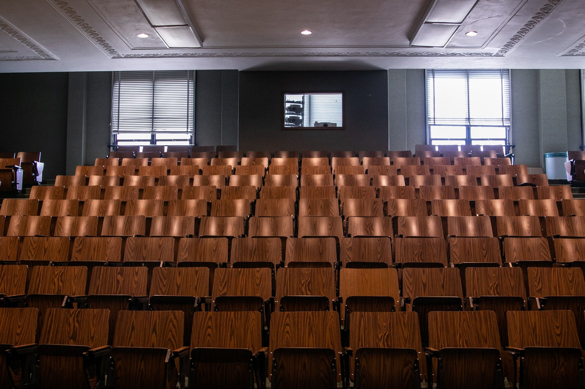A lecture hall with rows of wooden seats sits empty.