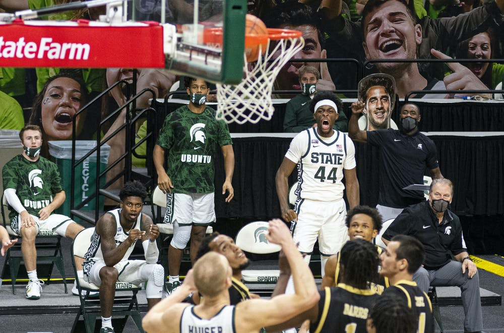 Junior forward Gabe Brown (44) and his Spartan teammates anticipate a three-pointer from Aaron Henry and start cheering in the second half of the game. The Spartans came back in the second half to end the game against the Broncos 79-61 on Dec. 6, 2020.