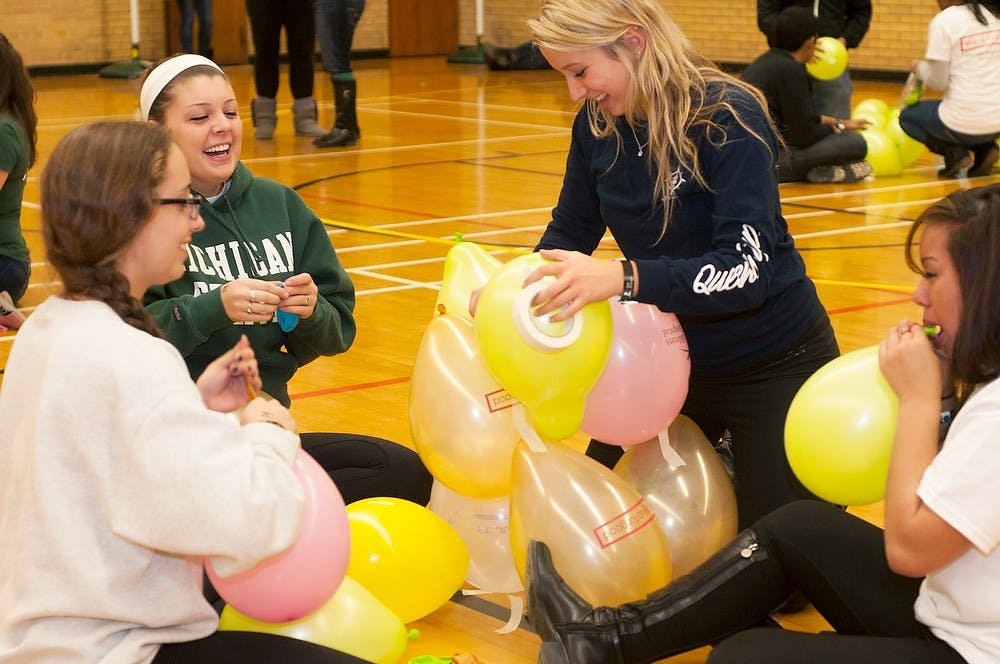 <p>From left, pre-medical freshman Jaqui Somes, no preference freshman Allison Sirosky, supply chain management freshman Jamie Ulanch and communications junior Michelle Francis build a balloon tower Nov. 15, 2013, at IM Sports Circle. Students stayed up all night playing games, watching videos and eating to celebrate their fundraising for St. Judes research hospital.</p>