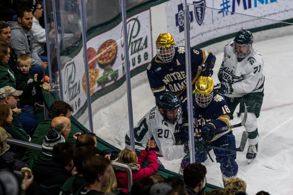 <p>Michigan State and Notre Dame players scrum in the corner trying to regain possession. The Spartans were defeated by the Fighting Irish, 2-1, on Nov. 22, 2019 at Munn Ice Arena.</p>