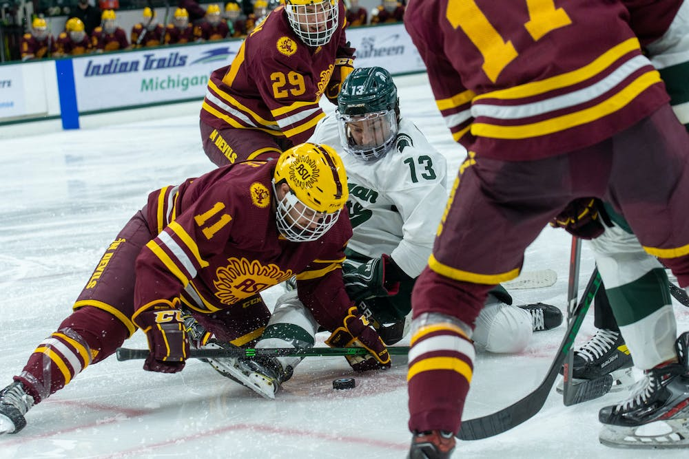 <p>Feb 14.- East Lansing- Michigan State Univeristy hockey player, Kristof Papp (13) during a face-off with Arizona State Univeristy hockey player Benji Eckerle (11).</p>