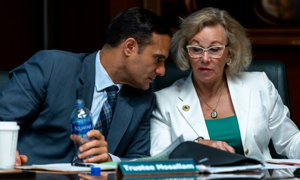 <p>Trustees Brian Mosallam (left) and Melanie Foster (right) speak to each other during an MSU Board of Trustees meeting June 21, 2019 at the Hannah Administration Building. </p>