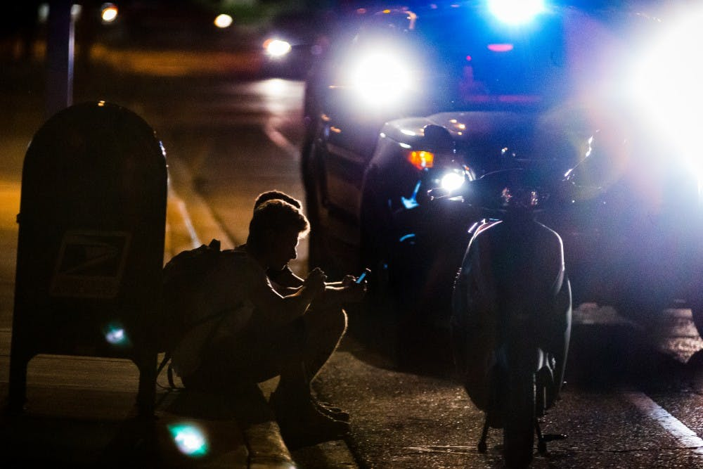 Two men sit on the curb after being pulled over on their moped on Sep. 2, 2017, on Abbot road.