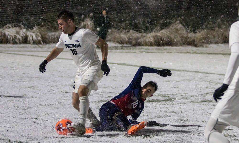 Senior defender Connor Corrigan (16) beats out a UIC player for the ball during the game against University of Illinois at Chicago at DeMartin Stadium on Nov. 15, 2018. The Spartans defeated the Flames, 2-0.