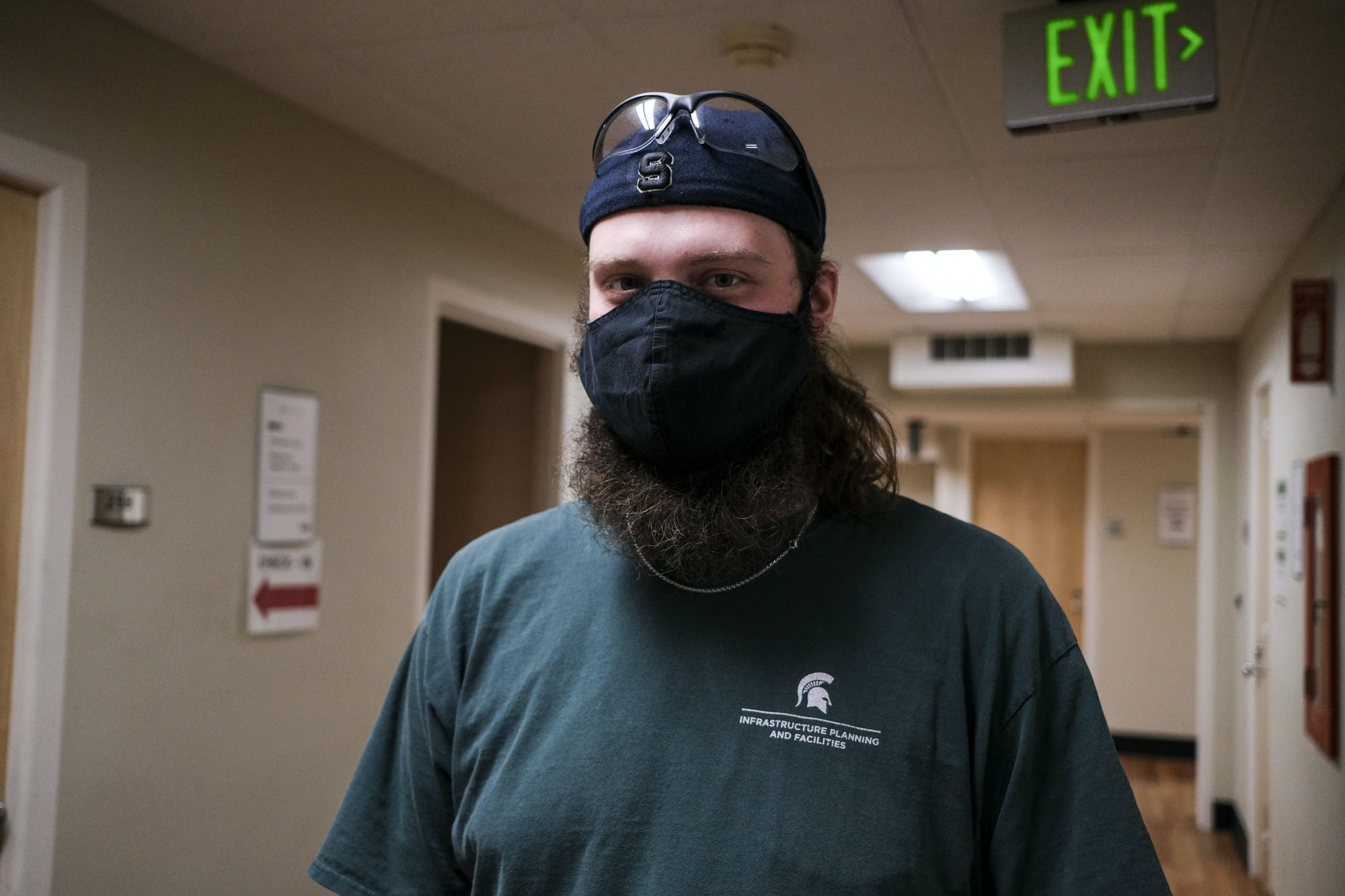 A bearded person wearing a face mask and a backwards cap with eye protection glasses resting on it stands in a hallway posing for a picture.