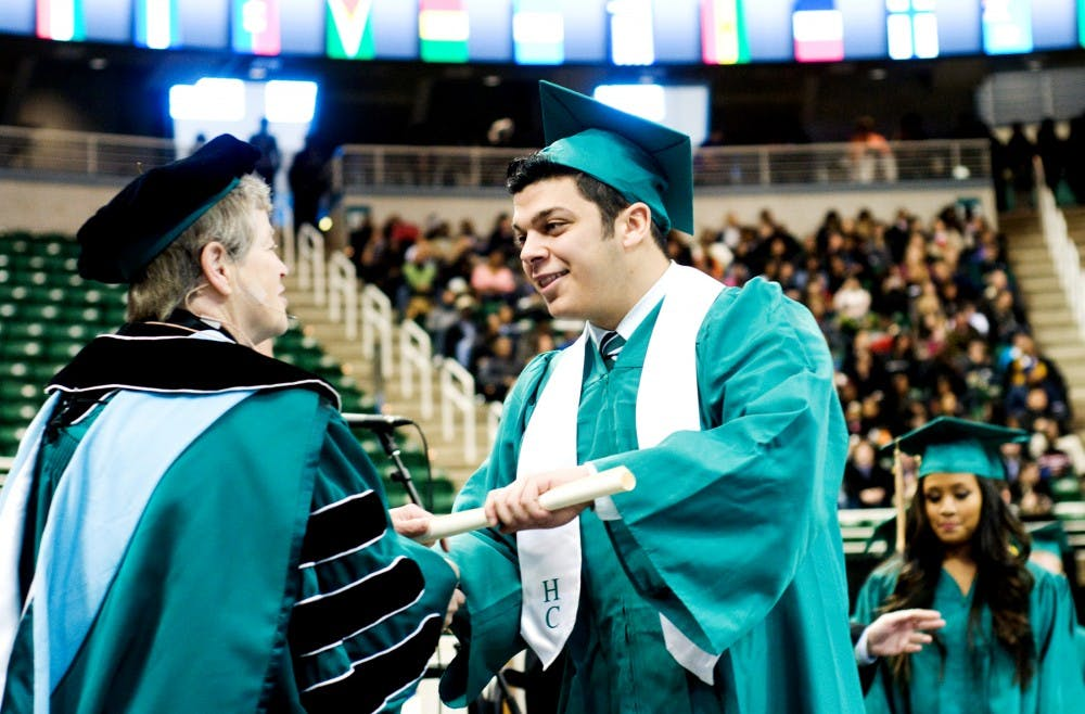 <p>Accounting student Ogeen Kada receives his bachelor&#x27;s degree from then-MSU President Lou Anna K. Simon at the Breslin Center during a commencement ceremony in 2011. Justin Wan/The State News</p>