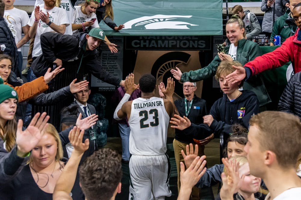 <p>Then-junior forward Xavier Tillman Sr. high-fives fans after a win over Iowa. The Spartans defeated the Hawkeyes, 78-70, at the Breslin Student Events Center on Feb. 25, 2020. </p>