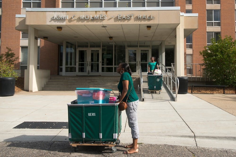 <p>Neuroscience and philosophy freshman Tamara Porter, center, waits for her parents Aug. 23, 2015, to help her move into her dorm in East Holmes Hall. Her niece Starr Alexander, 15, is in the background.</p>