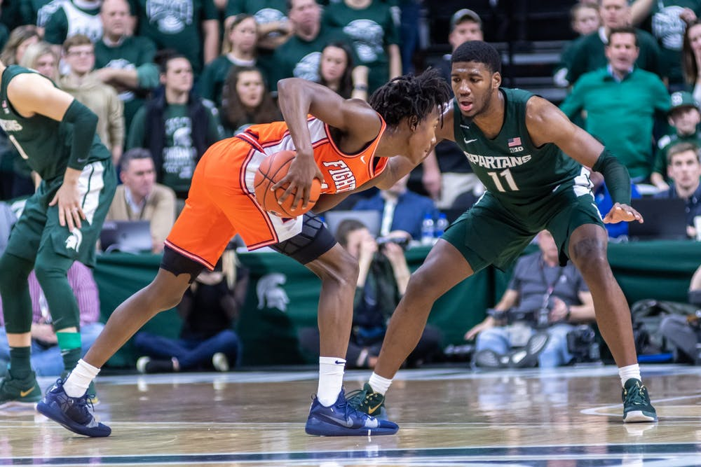 <p>Sophomore forward Aaron Henry (11) defends Illinois guard Ayo Dosunmu (left). The Spartans defeated the Illini, 76-56, at the Breslin Student Events Center on Jan. 2, 2020.</p>