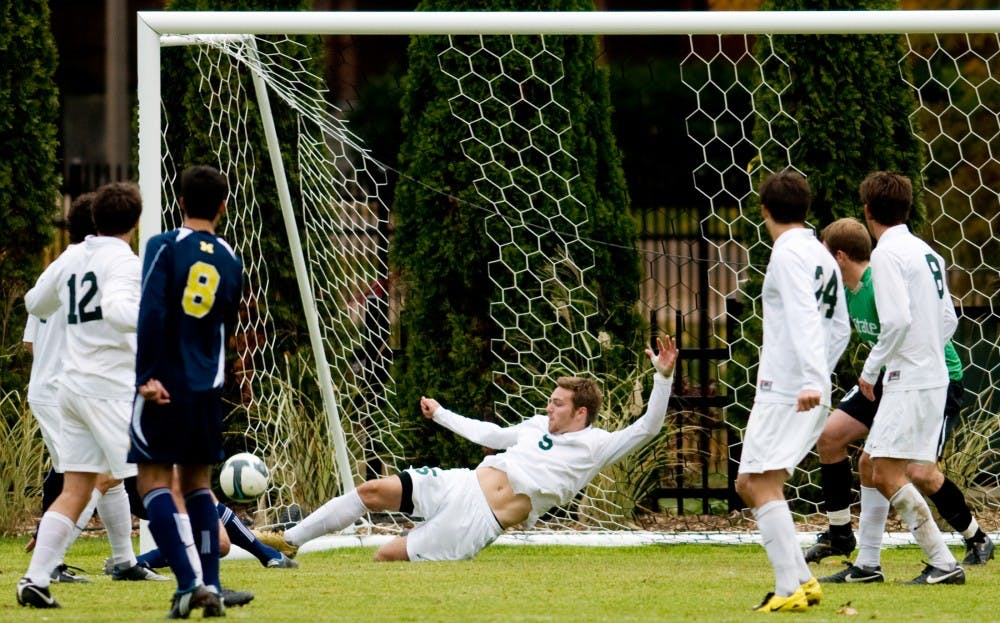 Then junior defenseman Colin Givens clears the ball away from the net preventing a goal against the Wolverines on Oct. 25, 2009 at DeMartin Stadium at Olde College Field. Givens, who was drafted by the Colorado Rapids, was a two-time All-Big Ten performer for the Spartans in three seasons. State News File Photo