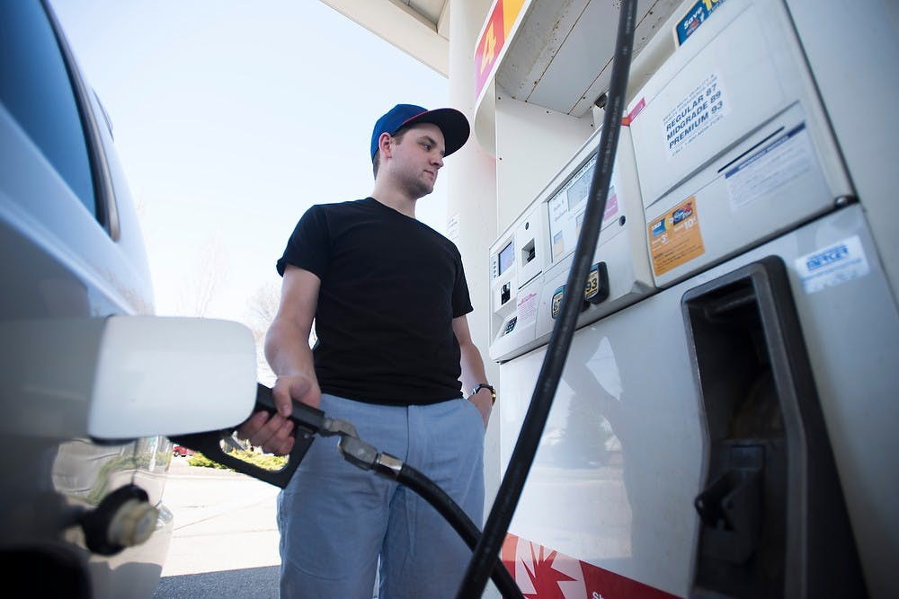 <p>Journalism junior and State News reporter Andy Merkle pumps his gas April 17, 2015, at the Shell gas station, 1831 E. Grand River Ave. Merkle spent about $35.01 on gas this month. </p>