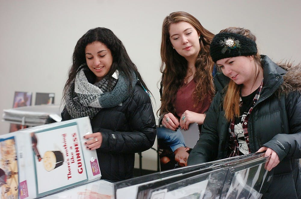 <p>Hospitality business sophomore Anna Margosian, Special education sophomore Christina Connolly, and nursing junior Catie Ray look at posters Jan. 14, 2015, during the poster sale at the MSU Union. Jessica Steeley/The State News</p>