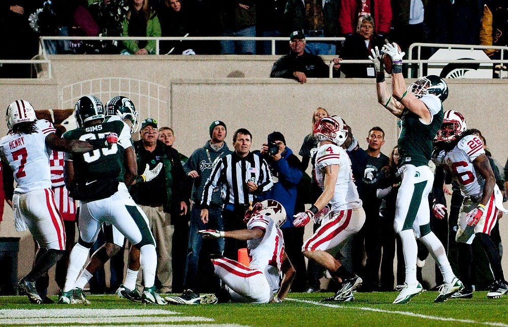 <p>Senior wide receiver Keith Nichol catches a tipped ball which he took to the endzone for the win over the Badgers. The Spartans defeated Wisconsin, 37-31, on Saturday night at Spartan Stadium. Josh Radtke/The State News</p>