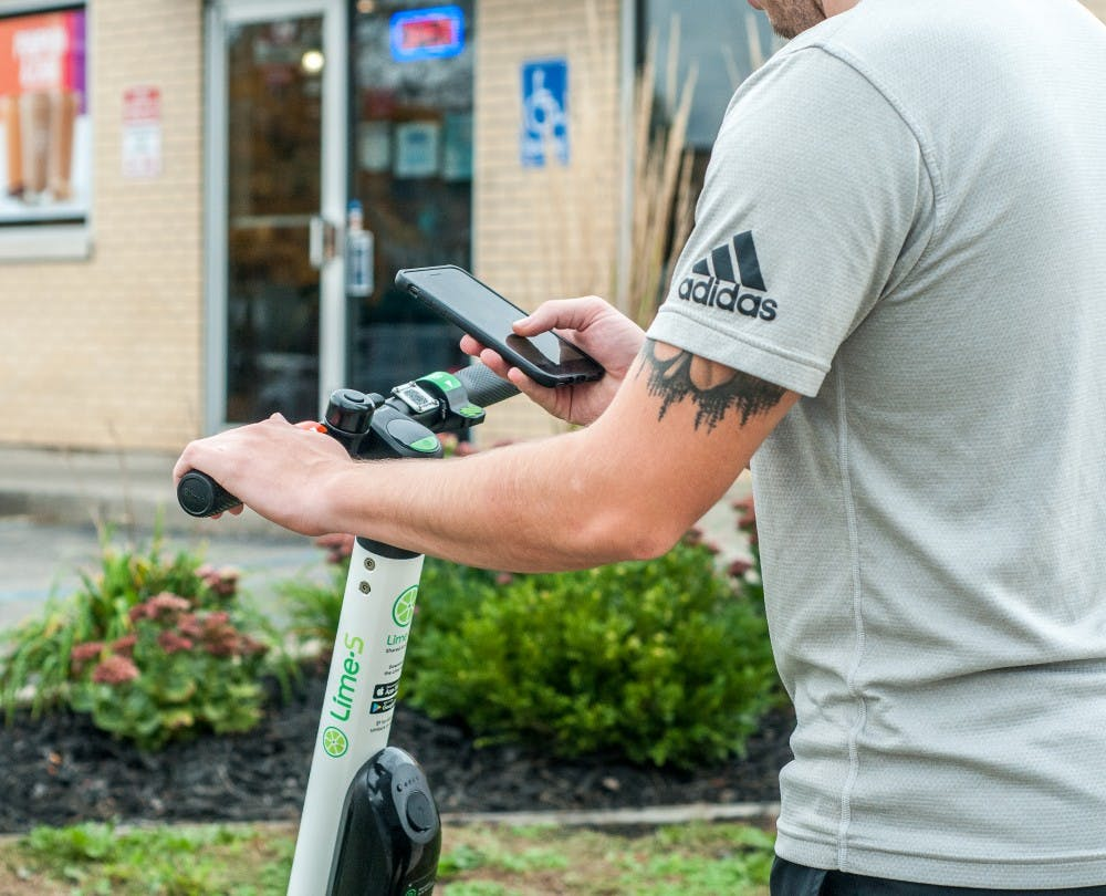 <p>Advertising management senior Dom Rea unlocks a Lime scooter using his phone Oct. 10, 2018, at Grand River Avenue.</p>
