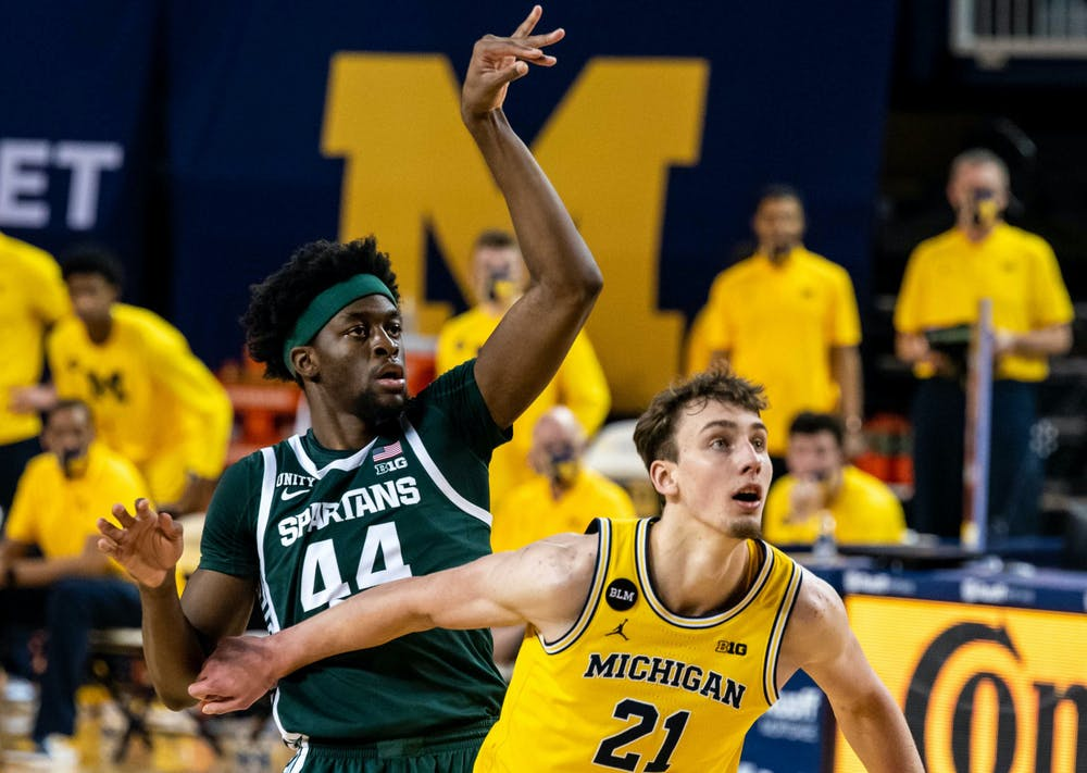 Junior forward Gabe Brown (44) shoots a free throw and is immediately shoved by a Michigan guard in the second half. The Wolverines crushed the Spartans, 69-50, at Crisler Center on Mar. 4, 2021.