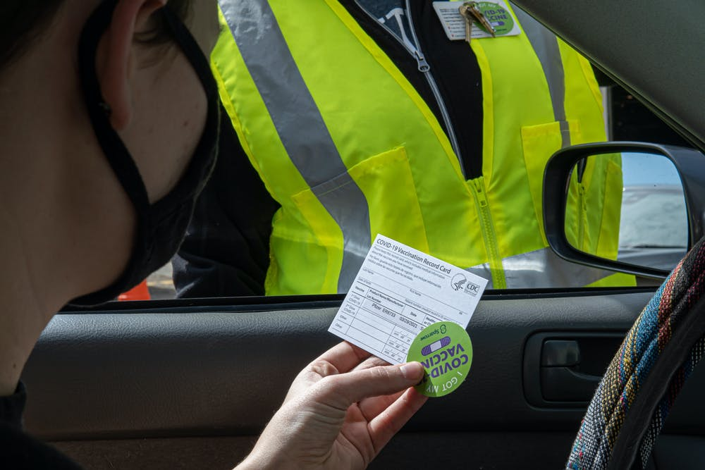 <p>Michigan State student Maddie Monroe is handed her vaccine card and a sticker after getting the COVID-19 vaccine on March 29, 2021.</p>