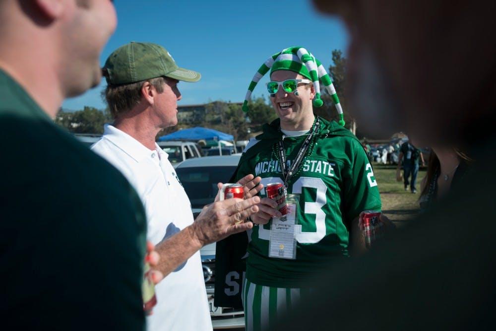 "<p><span class=""caps"">MSU</span> alumni John Cannon, left, and Jon Legg tailgate before the 100th Rose Bowl on Jan. 1, 2014, in Pasadena, Calif. Julia Nagy/The State News</p>"